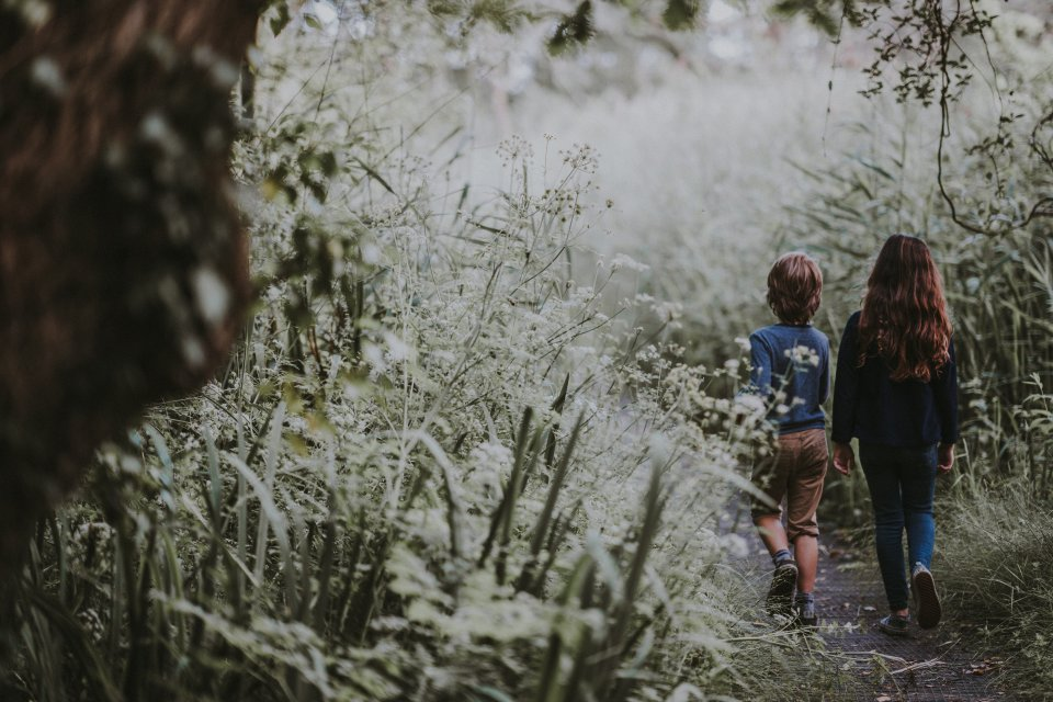 Two young children walking along a path in an overgrown field