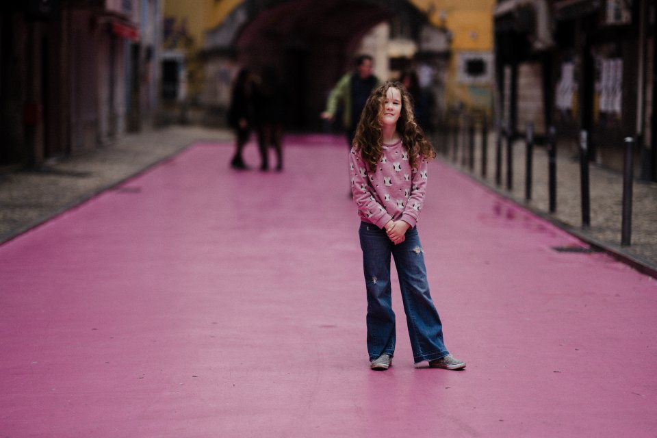 A young girl in jeans and a pink top standing on a pink road