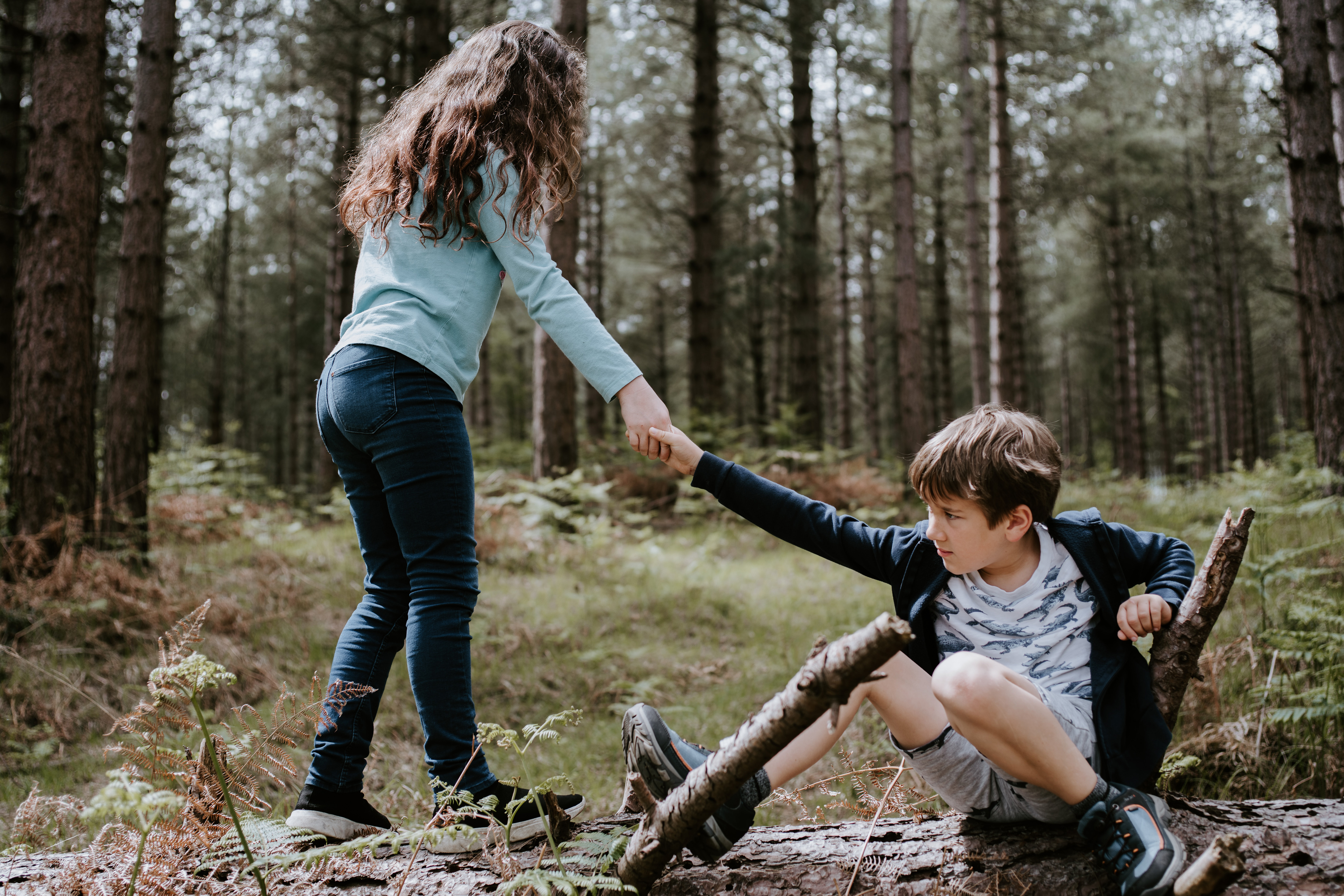 A young girl helping a young boy stand up. They are in some woods.