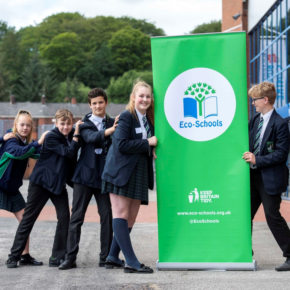 Children of various ages next to a Eco-Schools roll up banner